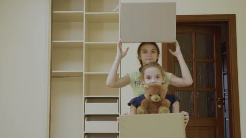 Two happy girls with boxes relocates in a new house Footage
