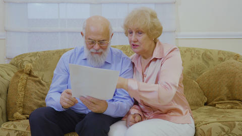 Senior couple looks on their rent bills sitting at sofa at home Footage