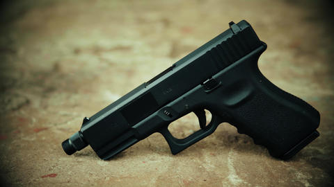View of a black handgun on a concrete background Footage