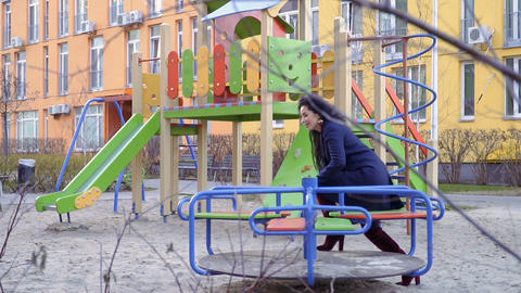 Happy woman rejoices at roundabout at the playground in slowmotion Footage