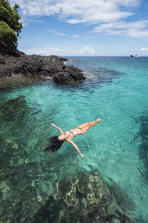 Attractive Mixed Race Woman in Bikini Lying on Clear Blue Water at Tropical Foto