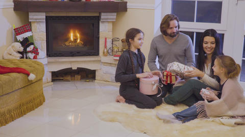Happy family exchanges christmas gifts near fireplace Footage