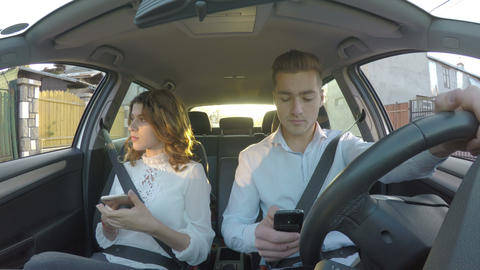 Driver and girlfriend in the car not paying attention to road both using smart Footage