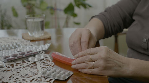 Hands of a married old woman preparing her daily medication doses in a pill Live Action
