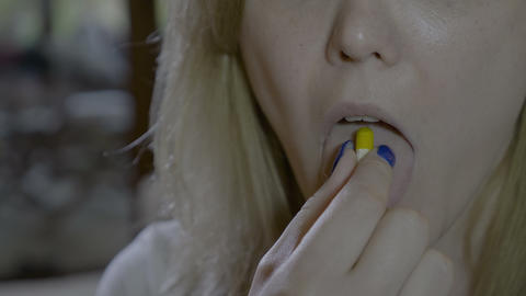 Close up of a sick woman mouth swallowing a yellow capsule pill of antibiotic Footage