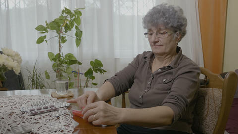 Elder woman arranging her medication in a pill organizer box and dropping one Live Action