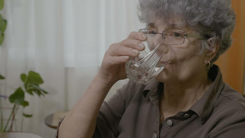 Senior old woman taking a pill swallowing and drinking a whole glass of water Footage