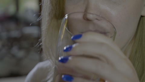 Close up of a young woman swallowing a round blue pill and drinking a glass of Footage