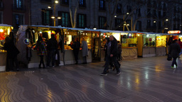 Rambla alley in dusk, panning shot, many stalls, people walk beside, dim light Live Action