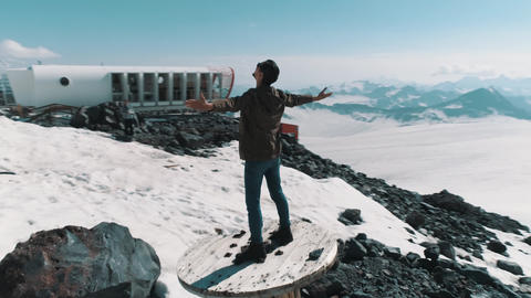 Aerial view man lifts arms standing on cable spool on stones at snowy mountains Footage
