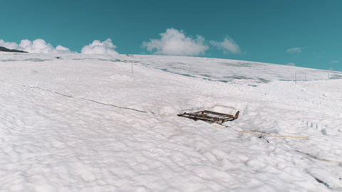 Aerial shot of mountain sidehill covered in snow and tracks Footage