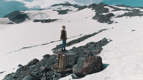 Aerial shot man spread arms standing on cable spool on rocks at snowy mountains Footage