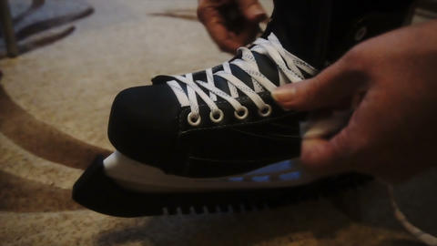 tying the white laces on skates,preparing to go on the ice Footage