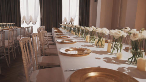 Glass plates and vases with roses on banquette table at luxurious hall 영상물