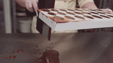 Pastry chef scrapes excessive chocolate off plastic mold Live Action