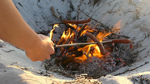 Three sausages are cooked on the campfire in summer in slo-mo Footage