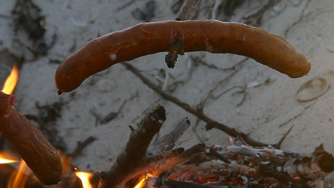Two sausages on a wooden stick are cooked on a campfire in slo-mo Footage