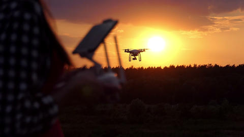 Young woman keeps a panel to manage her drone at sunset in slo-mo Bild