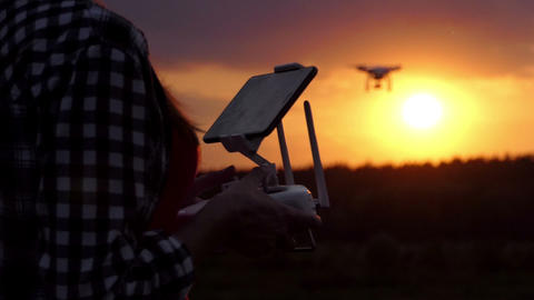 Smart woman keeps a panel to manage her drone at sunset in slo-mo Footage