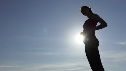 A beautiful pregnant woman caresses her belly at a sunset in slo-mo Footage