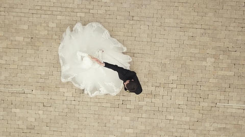 Young husband and wife spinning in wedding dance on paving square drone view 영상물