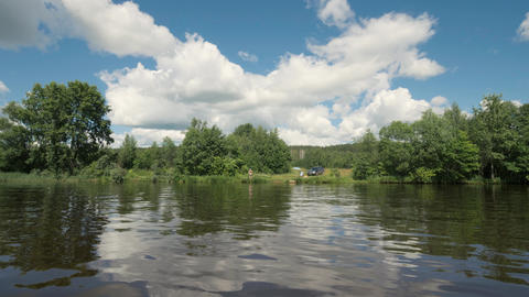 Panoramic view on river water to summer nature and people resting on shore Footage