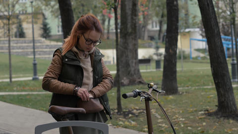 Woman cyclist opening lock on bicycle parking in city park Footage