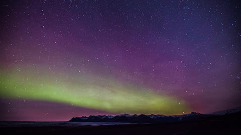 Time Lapse - Green and Pink Colored Northern Lights over the Mountains ビデオ