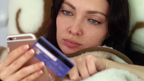 A woman is making a purchase with a credit card from bed ビデオ