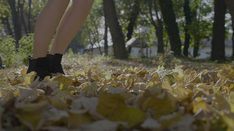 Young beautiful girl with long and toned legs running through autumn leaves in a Footage