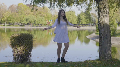 Beautiful young girl with long hair dressed in white clothes spinning near to a Footage