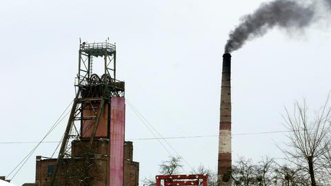 Industrial mine billowing smoke into blue skies 4k Footage