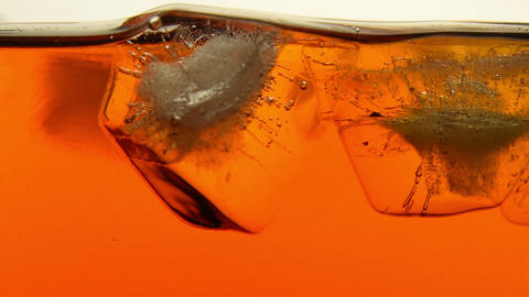 Ice cubes melt in tea or whiskey close up Footage