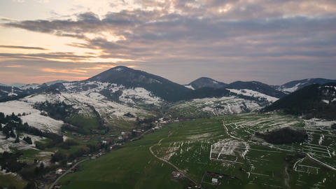 Evening colors over snowy rural landscape in early spring countryside. Aerial Footage