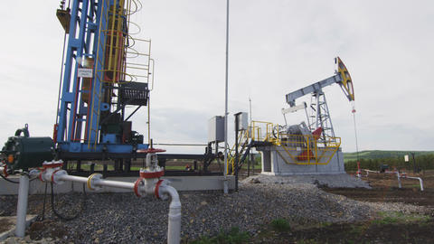 Pump Jack Operates at Oil Well against Cloudy Sky Footage