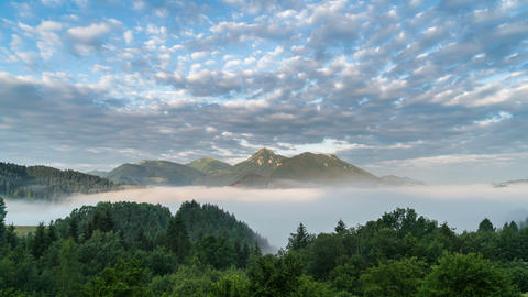 Clouds moving over blue sky and magic mountains landscape in foggy morning Footage