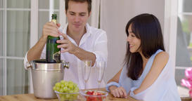 Smiling young couple pouring champagne to drink Footage
