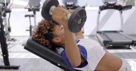 Concentrated sportswoman training with dumbbells Footage