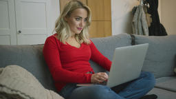 Smiling woman using laptop on sofa Footage