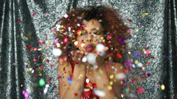 Ethnic woman blowing at confetti Footage