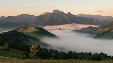 Sunbeams moving over foggy mountain valley at sunrise. Mist morning in beautiful Footage