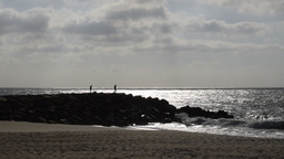 Two Figures On Beach Breakwater With Calm Sea And Clouds stock footage