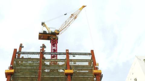 Tower crane hoisting I beam up side of building logos blurred 1 Live影片