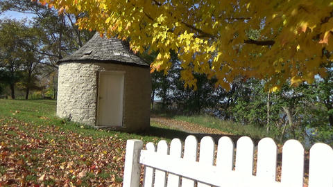 Autumn scenery with falling leaves, picket fences and a stone shack Footage