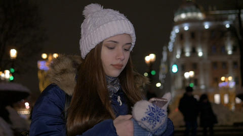 A girl in a white hat, in winter, walks down the street and reads a message on Live Action