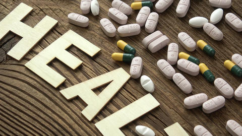 Pills with inscription HEALTH on brown wooden surface background Live Action