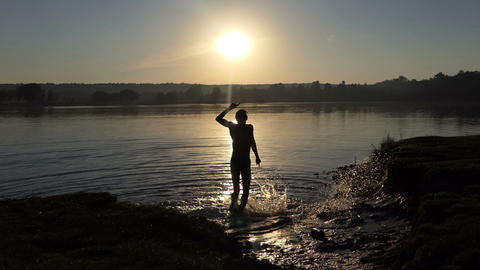 Happy teenager dances in a lake at sunset Footage