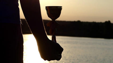 Man s hand keeps a winner bowl on a lake bank at sunset Live Action