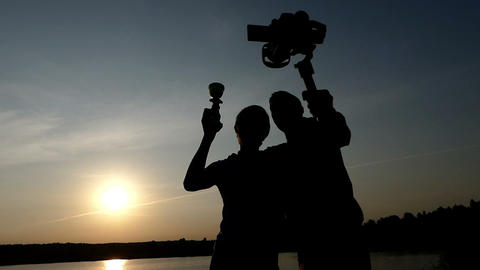 Two young men keeping a stedicam and a champion bowl at sunset ビデオ