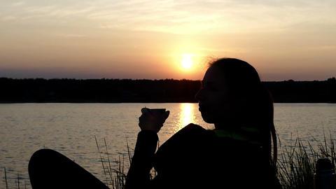 Young woman lies on a lake bank, drinks tea and laughs Image